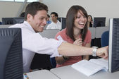 Happy Students Sitting Together At Computer Desk — Stockfoto
