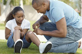 Father Sticking Bandage To Daughter's Knee At Park — 图库照片