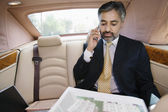 Businessman Looking At Notepad While On Call In Car — Stock Photo