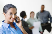 Businesswoman On Call With Colleagues Discussing In The Background — Stock Photo