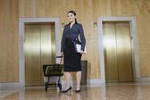 Businesswoman Pulling Trolley Against Elevators — Stock Photo