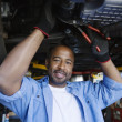 Auto Mechanic Beneath A Car - Stock Photo