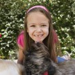 Dog Licking Little Girl's Chin - Stock Photo