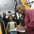 Teacher Unloading Elementary Students From School Bus — Stock Photo #21971849