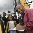 Teacher Unloading Elementary Students From School Bus - Stock Photo