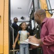 Teacher Unloading Elementary Student From School Bus - Stockfoto