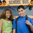 Teenagers By School Bus - Stock Photo