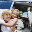 Grandmother Hugging Granddaughter By Minivan — Stock Photo
