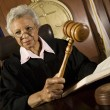 Judge Holding Gavel In Courtroom - Stock Photo