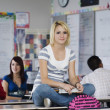 Female Student Sitting On Bench In Classroom — ストック写真