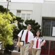High School Couple Walking in Front of School — ストック写真
