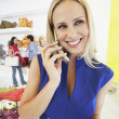 Woman Using Mobile Phone In Store — Stock Photo