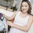 Expectant Woman Packing Baby Clothes — Stock Photo #21977743