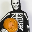 Child In Skeleton Costume Holding Jack-O-Lantern — Stock Photo