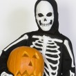 Kid In Skeleton Costume Holding Jack-O-Lantern - Stock Photo