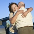 Senior Couple Hugging In Front Of Car — Stock Photo