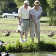 Happy Senior Couple Feeding Ducks — Stock Photo #21978227