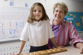 Teacher And Schoolgirl With Counting Tray — Stock Photo