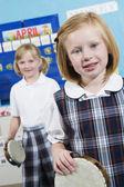 Mädchen mit tamburin in musik klasse — Stockfoto