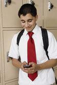 High School Boy Text Messaging By School Lockers — Stock Photo