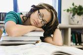 Lise öğrencisi bir kitap yığını üzerinde uyuyor — Stok fotoğraf