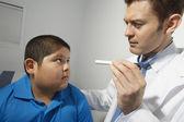 Doctor examining boy's eye — Stock Photo