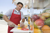Male Street Vendor Chopping Fruits — Stock Photo