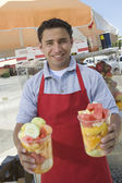 Male Street Vendor Holding Fresh Fruit Salads — Stock Photo