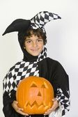 Little Boy In Jester Outfit Holding Jack-O-Lantern — Stock Photo