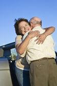 пожилые супружеские пары обнимать перед автомобилем — Стоковое фото