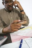 Man Using Cell Phone While Holding Credit Card — Foto de Stock