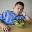 Unhappy preadolescent Boy Sitting At Desk With Salad — Stock Photo #22150997