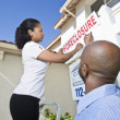 Real Estate Agents Putting For Sale Notice Outside House — Stock Photo