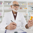 Pharmacist Working In Pharmacy - Stock Photo