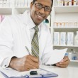 Stock Photo: Male Pharmacist Working In Pharmacy