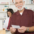 Stock Photo: MPicking Up Prescription Drugs At Pharmacy