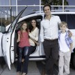 Happy family next to white car — Stock Photo #22152067