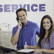 Portrait of man and woman standing in auto repair shop — Stock Photo