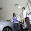 Car salesman shaking hands with female customer in showroom — Stock Photo