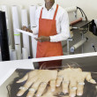 Man working at printing press with photo printouts on table — Foto Stock