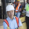 Stock Photo: Portrait of warehouse manager with arms crossed and colleagues in background