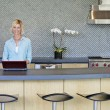 Portrait of smiling senior woman using laptop in kitchen - Foto Stock