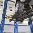 Stock Photo: Low angle view of mechanic working under car