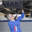 Stock Photo: Car mechanics working below car using monkey wrench