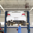 Foto Stock: Mechanic checking underneath car on lift