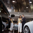 Woman standing with auto salesman in showroom — Stock Photo