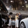 Woman standing with auto salesman in showroom — Stock Photo #22153031