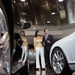 Woman standing with auto salesman in car showroom - Stock Photo