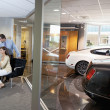 Stock Photo: Womand salesmsitting in car showroom office