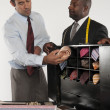 Stock Photo: Mselecting neckwear while shop owner standing besides him